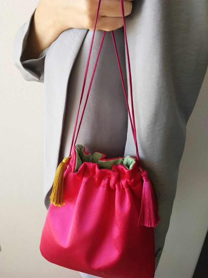 bolso de mano mujer fucsia rosa con borlas amarillas
