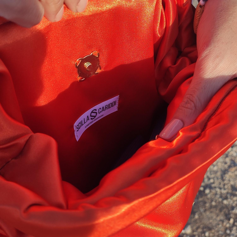 interior-bolso-clutch-mano-naranja-verano